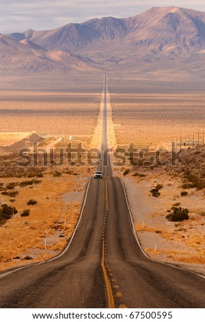 Long desert highway leading into Death Valley National Park from Beatty, Nevada - stock photo