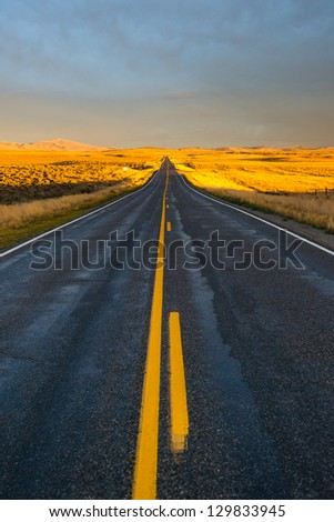 Long desert highway to the mountains - stock photo
