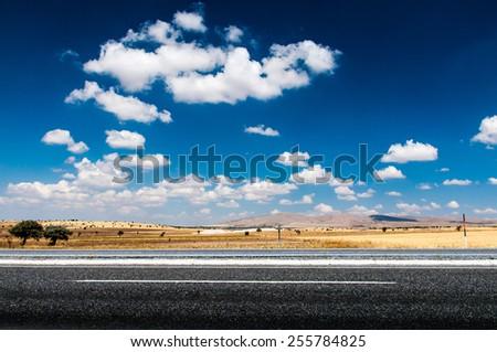 Long desert highway under the hot sun. - stock photo