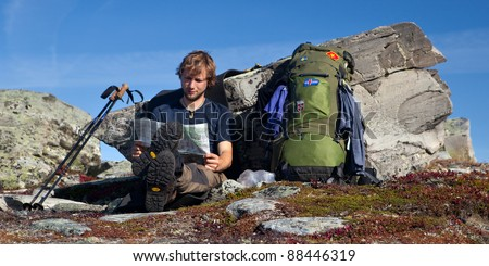 long distance hiker have a break and looks to the map - stock photo