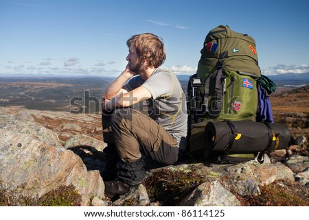 Long distance hiker have a break on the top of the mountain - stock photo