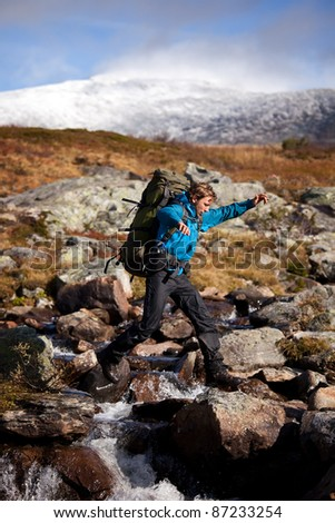 Long distance Hiker jumped over a little river - stock photo