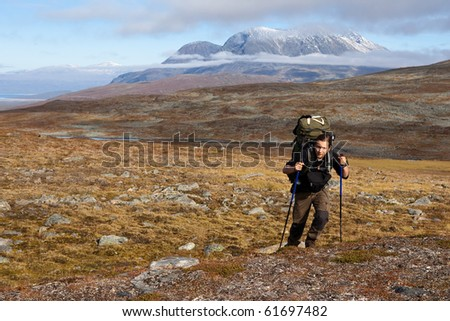 long distance hiker with backpack on the trail in Laponia - stock photo