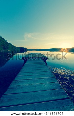 Long dock at dusk on calm and gentle lake in fisheye nature shot - stock photo