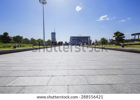 long empty footpath in modern city square with skyline. - stock photo