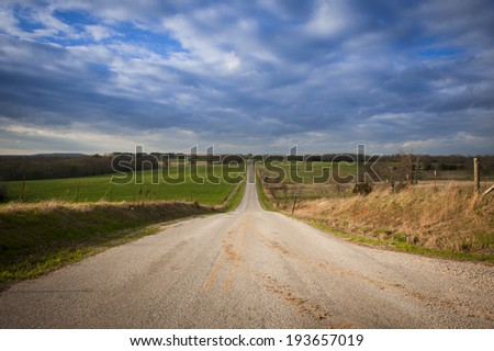 Long empty highway with cloudy sky.  - stock photo