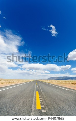 Long empty road running to the far horizon - stock photo