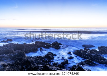 Long exposure at sunset (golden hour) on a rocky shoreline, with waves breaking over the rocks, traveling the Big Sur Highway, on the California Central Coast, near Cambria CA. - stock photo
