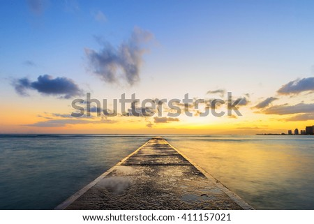 Long exposure at sunset of cement pier jutting out into Pacific Ocean during sunset golden hour - stock photo