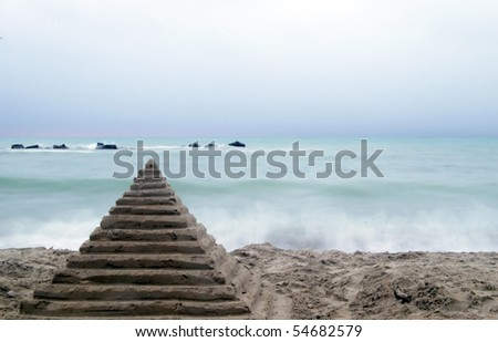 Long exposure beach with sand pyramid in front - stock photo