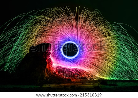 Long exposure burning and spinning of steel wool - rainbow colors digital manipulation. - stock photo