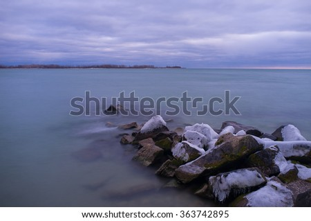 long exposure cloudy sky, ice top rock in the lake  - stock photo