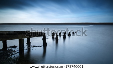 Long exposure landscape of old jetty extending into lake - stock photo