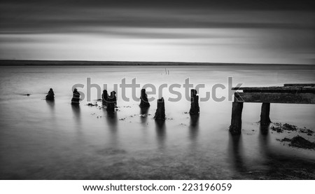 Long exposure landscape of old jetty extending into lake  black and white - stock photo