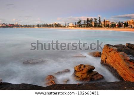long exposure makes aqua green blue mystical ocean sea waves swirling around rocks as sun rises over Manly Beach, Sydney, NSW, Australia - stock photo