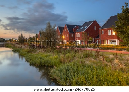 Long exposure night image of a suburban Street with modern ecological middle class family houses with eco friendly river bank in Veenendaal city, Netherlands. - stock photo