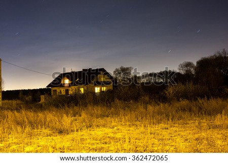 Long exposure night photograph of alone house in field