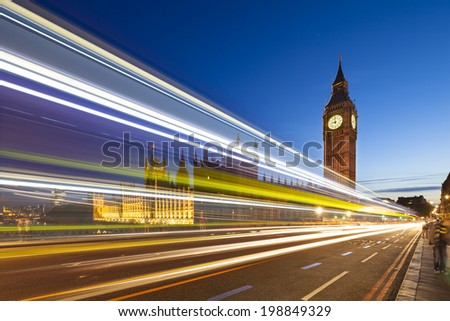 Long exposure night shot of the Houses of Parliament in London with blue sky and a bus passing on Westminster Bridge in the foreground.