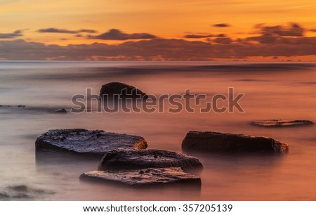 Long exposure ocean sunset. Crimson sunset with waves and clouds motion blurred and flat rocks in the foreground - stock photo