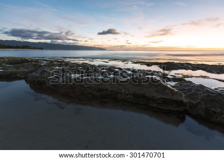Long exposure of a beach with smooth waters on the north shore of Oahu, Hawaii during dusk. Tide pools in the foreground and the western tip of the island on the horizon.  - stock photo