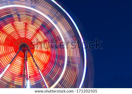 Long exposure of a colorful and illuminated ferris wheel at night. - stock photo