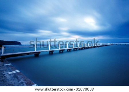 Long exposure of a Jetty with a dramatic sky. - stock photo