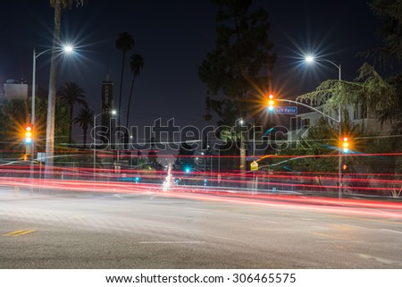 Long exposure of a street in Los Angeles at night with light trails from automobiles.  Red, yellow, and green lights appear at the same time on the traffic light. - stock photo