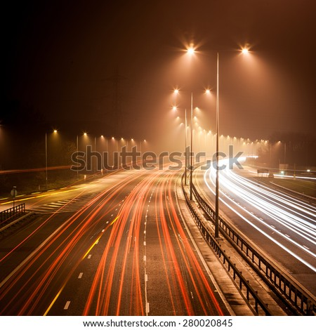 Long exposure of a UK motorway with trails of light of passing vehicles. - stock photo