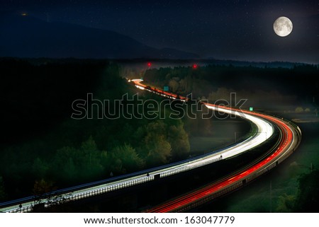 Long Exposure of Car Lights on Motorway Car Lights on Motorway with Moon, stars and green forrest - stock photo