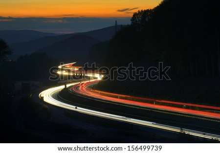 Long Exposure of Car Lights on Motorway Meandering through Hills at Sunset - stock photo