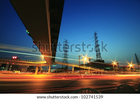 Long exposure of cars passing through of the city-highway and transmission tower - stock photo