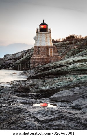 Long exposure of Castle Hill Lighthouse seascape in the morning with a beacon reflection in the water. / Castle Hill Lighthouse - stock photo