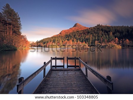 Long exposure of Glencoe Lochan in autumn, with jetty and the pap of Glencoe in the distance. - stock photo