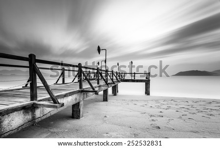 Long exposure of magic sunrise and wooden pier, Nha Trang City Beach, Vietnam - stock photo