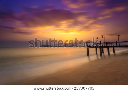 Long exposure of magic unreal colorful sunrise and wooden pier, Nha Trang City Beach, Vietnam - stock photo