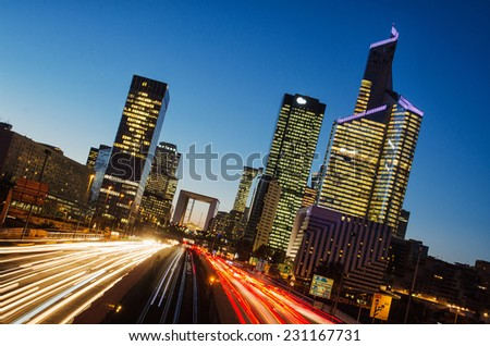 Long exposure of multi-lane road with skyscrapers of business district La Defense, Paris, France in the background - stock photo