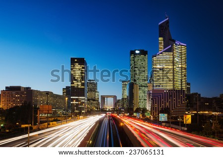 Long exposure of multi-lane road with skyscrapers of business district La Defense, Paris, France in the background