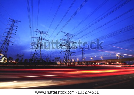 long exposure of night car rainbow light traffic on a highway and transmission tower at night skyline - stock photo