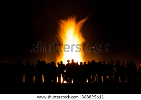Long exposure of people watching a bonfire at night, slight motion blur to people and the fire - stock photo