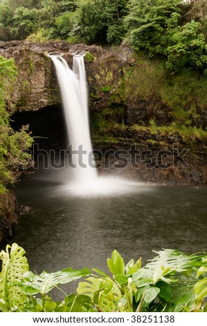 Long exposure of scenic Rainbow Falls of the Wailuku River, nestled among the lush green rainforest, near Hilo, Hawaii - stock photo