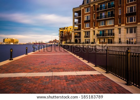 Long exposure of the Waterfront Promenade and condominiums in the Inner Harbor, Baltimore, Maryland. - stock photo