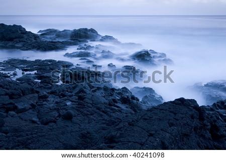 Long exposure of waves crashing on rocky lava coast at dusk, in the Big Island of Hawaii - stock photo