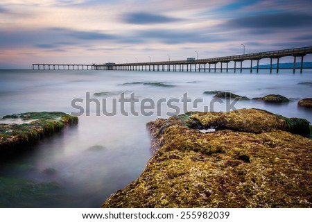 Long exposure of waves on rocks and the fishing pier in Ocean Beach, California. - stock photo