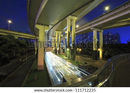 Long exposure photo High-speed urban viaduct construction background at night - stock photo