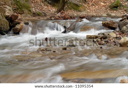 Long exposure photo of a river in the forest - stock photo