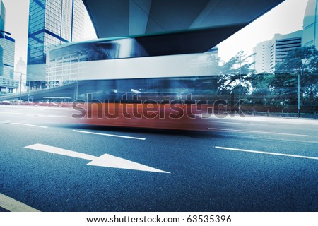 Long exposure photo of bus moving on urban road. Motion blur over city background. Cross processed colors. - stock photo