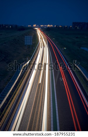 Long exposure photo of traffic on the move at dusk - stock photo