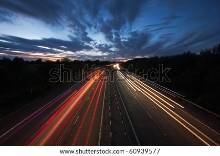 Long exposure photo of traffic on the move at dusk on the M40 motorway in England. - stock photo