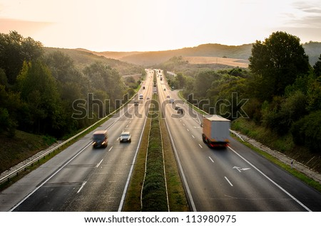 Long exposure photo of traffic on the move at sunset - stock photo
