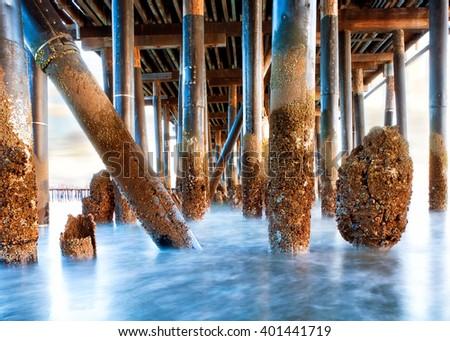 Long exposure photo of waves under Stearn's Wharf in Santa Barbara, California USA - stock photo